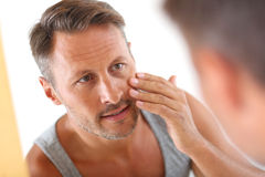 Man applying cream on face Royalty Free Stock Image
