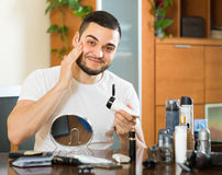 Man applying cream on face skin Royalty Free Stock Images