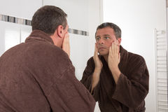 Man applying cream at his face and looking at himself Stock Images