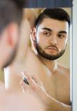 Man applying deodorant Stock Photos