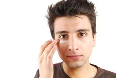 Man applying eye cream Royalty Free Stock Photography