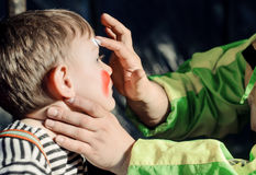 Man applying face paint to a little boy Royalty Free Stock Photos