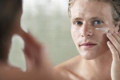 Man Applying Facial Cream. Mirror reflection of a young man applying facial cream on face Stock Image