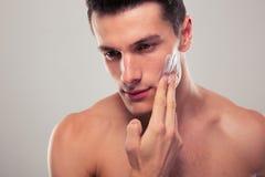 Man applying facial cream. Handsome man applying facial cream over gray background Stock Image