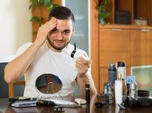 Man applying facial cream at home Stock Photo