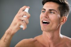 Man applying fresh breath spray royalty free stock photography