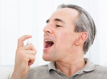 Man applying fresh breath spray. Close-up of a man applying Fresh breath spray Royalty Free Stock Images