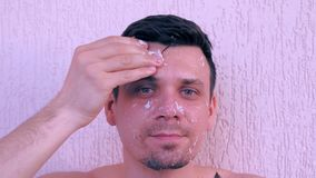 Man is applying fresh homemade coconut scrub on the face from coconut shell. Portrait of young handsome man is applying fresh homemade coconut mask on the face stock footage