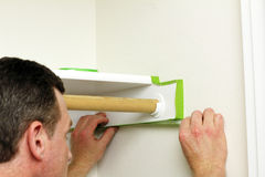 Man Applying Green Painter's Tape. A man is preparing to paint the closet walls by putting on green painter's tape to the edges around a shelf royalty free stock image