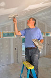Man applying joint compound. To seams between drywall panels on a ceiling royalty free stock image
