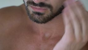 Man applying lotion on beard in bathroom, skin care, cosmetics for men, close up