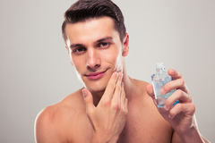 Man applying lotion after shave on face Stock Photography