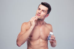 Man applying lotion after shave on face Royalty Free Stock Photography