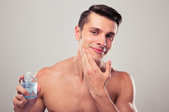 Man applying lotion after shave on face Royalty Free Stock Images