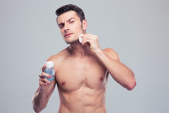 Man applying lotion after shave on face Royalty Free Stock Photo