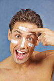 Man applying lotion to skin in face Stock Photo
