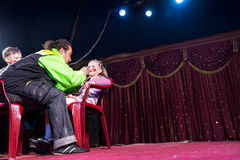 Man Applying Make Up to Girls Face on Empty Stage Royalty Free Stock Photos