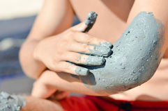 Man applying mineral blue mud on elbow Royalty Free Stock Photos