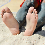 Man applying mineral blue mud on knee on summer sandy outdoors background Royalty Free Stock Photography