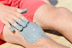 Man applying mineral blue mud on knee Royalty Free Stock Photography