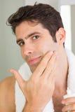Man applying moisturizer on face Stock Images