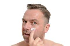 Man applying moisturizer to his skin Stock Photo