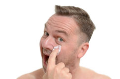 Man applying moisturizer to his skin Stock Photography