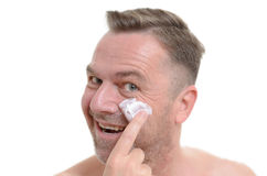 Man applying moisturizer to his skin Stock Photos