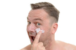 Man applying moisturizer to his skin Stock Images
