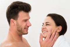 Man applying moisturizer on woman's cheek Stock Photography