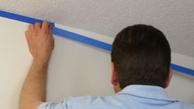 Man Applying Painter's Tape. Man preparing to paint a white ceiling by masking off the wall beneath it with blue painter's tape stock footage