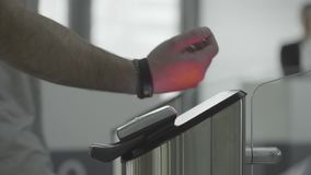 Man applying RFID bracelet to the electronic access equipment on entrance gate to the subway, underground or gym. Frame stock video footage