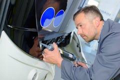 Man applying sealant to front bus Royalty Free Stock Photo