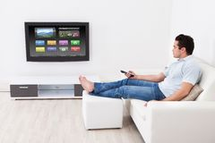 Man applying settings on television. Young Man At Home Applying Setting Of Television Sitting On Couch Royalty Free Stock Photos