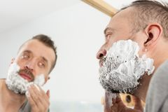 Man applying shaving cream on beard. Man preparing his facial hair before trimming his beard, applying shaving cream foam mousse. Male beauty treatment concept royalty free stock image