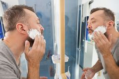 Man applying shaving cream on beard. Man preparing his facial hair before trimming his beard, applying shaving cream foam mousse. Male beauty treatment concept stock image
