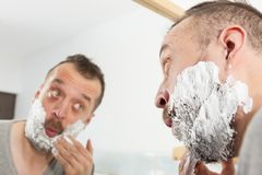 Man applying shaving cream on beard. Man preparing his facial hair before trimming his beard, applying shaving cream foam mousse. Male beauty treatment concept royalty free stock photos