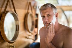 Man applying shaving cream on his face in cottage during safari vacation Stock Photography
