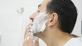 Man applying shaving foam on face skin, skincare and hygiene, morning ritual.  stock video