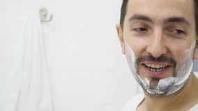 Man applying shaving foam on face skin, skincare and hygiene, morning ritual.  stock video footage