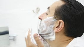 Man applying shaving foam on face skin, skincare and hygiene, morning ritual.  stock footage