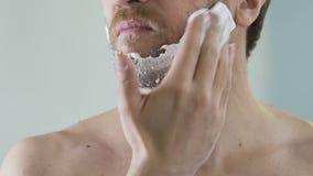 Man applying shaving foam on face skin, skincare and hygiene, morning ritual. Stock footage stock video