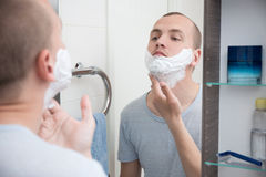 Man applying shaving foam to his face in bathroom Stock Photos