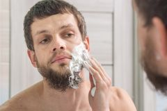 Man is applying shaving foam to his face preparing to shave Stock Photo
