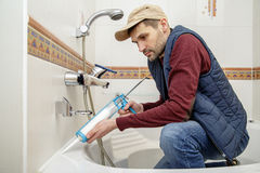 Man applying silicone sealant in the bathroom. Stock Photo