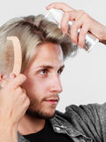 Man applying spray cosmetic to his hair Royalty Free Stock Photo