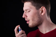 Man applying spray for sore throat. Horizontal Royalty Free Stock Photo