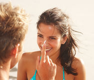 Man applying sun cream on his girlfriend's nose Royalty Free Stock Photo