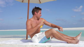 Man Applying Sun Lotion On Beach Holiday. Man applies sun lotion spray before lying down on towel.Shot on Canon 5d Mk2 with a frame rate of 30fps stock video
