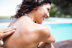 Man applying sunscreen on back of her woman  Stock Photography